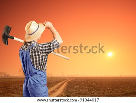 A male farmer holding a shovel and looking at a sunset - stock photo