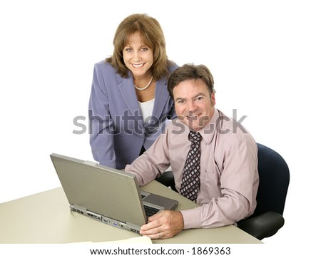 A male female business team working together on the computer.  Both are smiling.  Isolated on white.