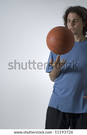 A male figure balancing a basketball on two fingers.  He is staring at the ball. Vertically framed shot.