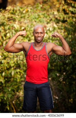 A male flexing his biceps - isolated against a green - stock photo
