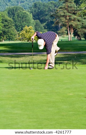 A male golfer bends to retrieve his ball from the hole. Space for copy in foreground. - stock photo