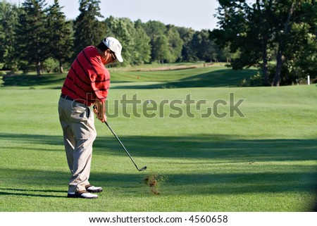 A male golfer hits a ball - turf flying and ball visible in flight. - stock photo