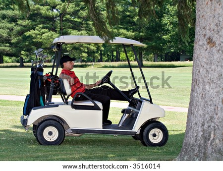 A male golfer in a golf cart sits under shady tree waiting for his turn. - stock photo