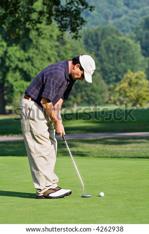 A male golfer lining up a putt on the golf green. - stock photo