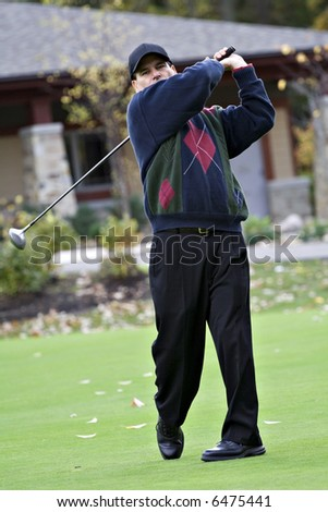 A male golfer playing a round on a fall day. - stock photo
