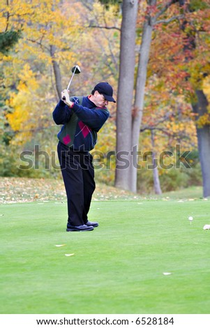 A male golfer plays a game on a beautiful fall day. - stock photo