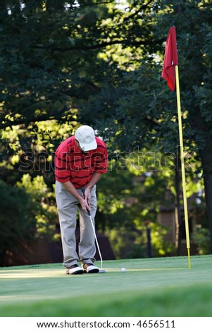 A male golfer putting on golf course green - red flag.