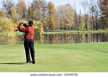 A male golfer smartly dressed in a red sweater is enjoying  a round of November  golf. - stock photo