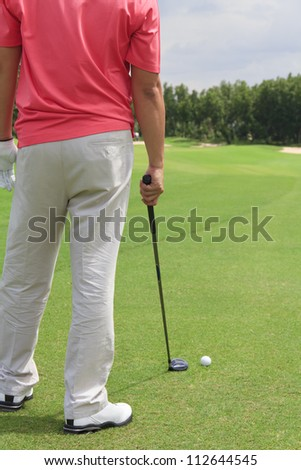 A male golfer standing. Planning for his next shot with a golf club in his hand. - stock photo