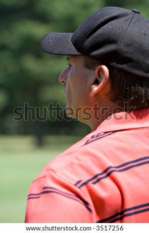 A male golfer studying the lay of a golf course - portrait, profile. - stock photo
