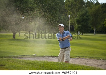 A male golfer takes a swing at his ball in a sand trap and creates a big spray of sand. - stock photo
