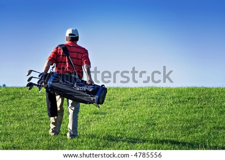 A male golfer walks the golf course - carrying bag of clubs and equipment.  Lomo effect. - stock photo