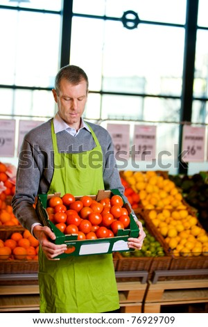 A male grocery owner with a box of ripe tomatoes - stock photo