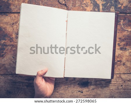 A male hand and a big notepad on a wooden table - stock photo