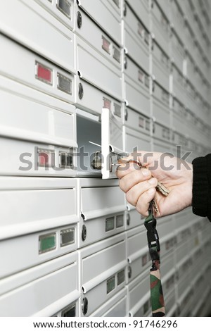 A male hand holding a bunch of keys opening a mailbox