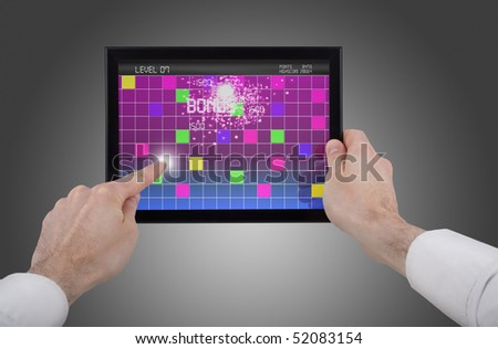 a male hand holding a touchpad pc, one finger touches the screen playing a retro arcade game