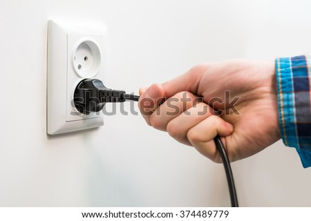 A male hand is pulling an electrical cord plugged into a socket - stock photo