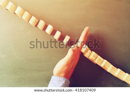 a male hand stopping the domino effect. retro style image. executive and risk control concept - stock photo