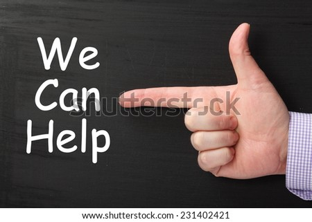 A male hand wearing a business shirt pointing a finger at the phrase We Can Help written on a blackboard
