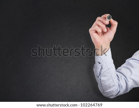 A male hand writing with a marker isolated on a dark background - stock photo
