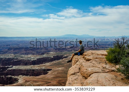 A male hiker sitting on the ledge of a large rock looks over the vast white rim trail