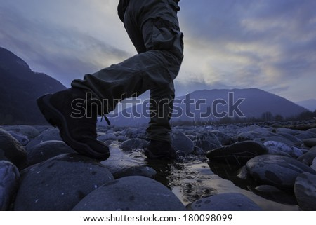 A male hiker walks across boulders on a river bed. Low angle view./ Hiker walking through river - stock photo