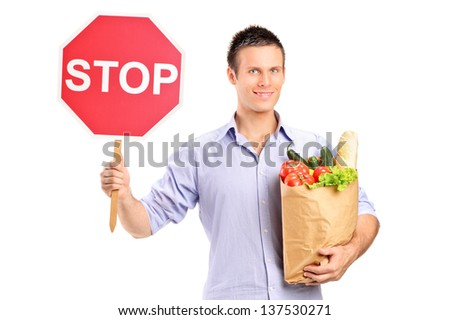 A male holding a paper bag and a stop road sign isolated on white background  - stock photo