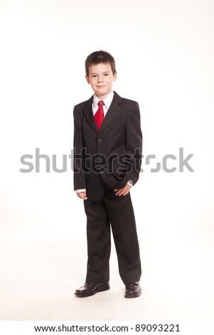 A male kid with red tie and a business-style suit posing in studio on white