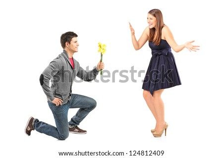 A male kneeling with flowers and his excited girlfriend isolated on white background - stock photo