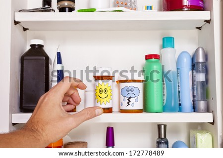 A male left hand reaches into a medicine cabinet for a pill container. - stock photo