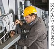 A male maintenance engineer at work on an industrial appliance - stock photo
