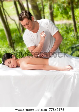 A male masseur giving a massage to a woman outdoors - stock photo