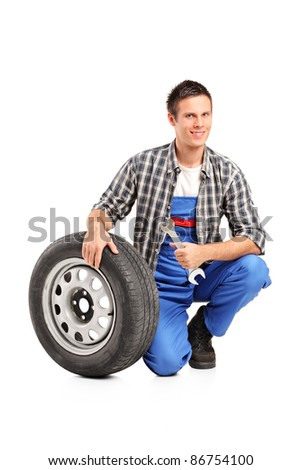 A male mechanic posing with a spare tire and holding a wrench isolated on white background