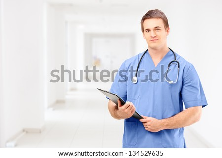 A male medical doctor in a uniform holding a clipboard and posing in a hospital corridor - stock photo