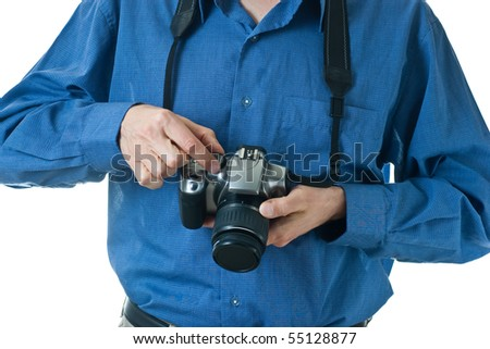 A male mid-section, wearing a blue dress shirt, holding onto an SLR camera, making adjustments to the dial.