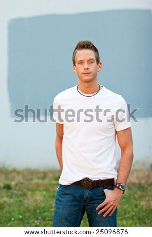 A male model looks directly at the camera with his hands in his pockets while wearing a white tee shirt. - stock photo
