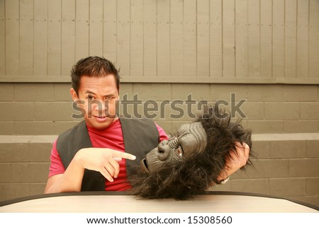 a male model makes a face at the request of the photographer to wear his Gorilla Costume Head - stock photo