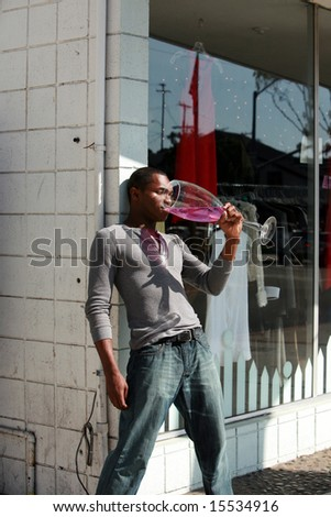 a male models relaxes with a Giant glass of wine after a hard day of modeling