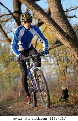 A male mountain biker on a single track trail in the woods. - stock photo