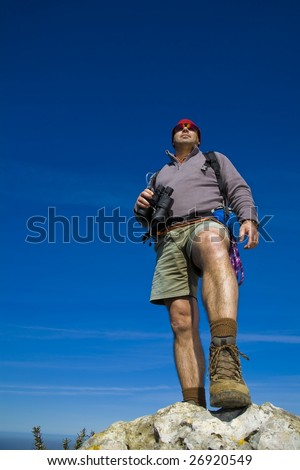 A male Mountain guide watching from above over a rock - stock photo