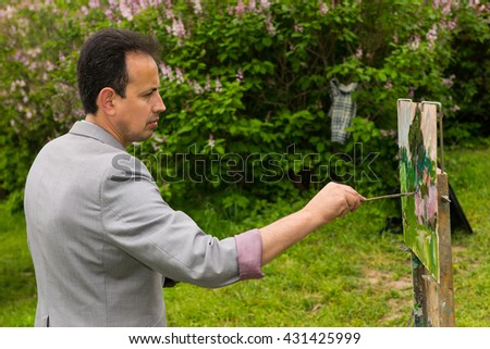 A male painter with his sketchbook in the park  working  on a trestle and easel painting with oils and acrylics during an art class - stock photo