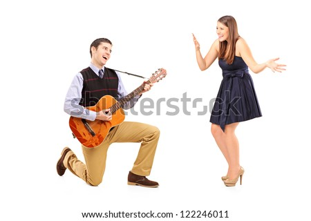 A male playing on a guitar and singing to his girlfriend isolated against white background