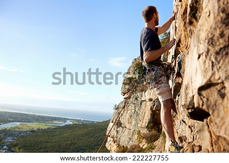 A male rockclimber climbing up a steep mountain attached to a rope and harness looking at the view - stock photo
