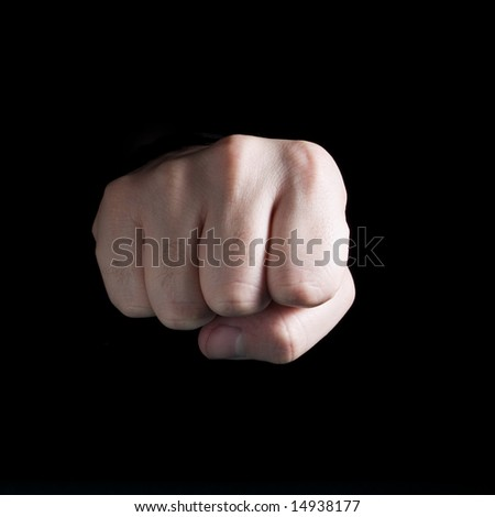 A male´s fist isolated on black background.