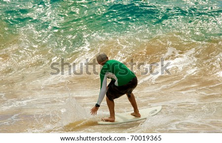 A male skimboarding on a beach in Maui - stock photo