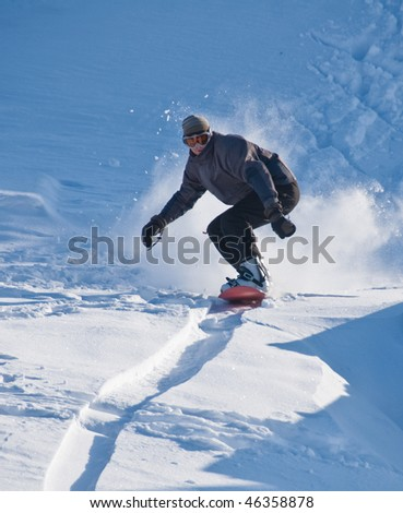 A male snowboarder speeding downhill, snow flying