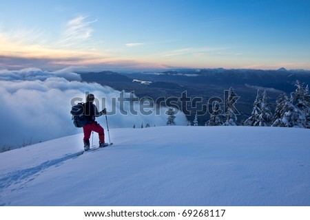 A male snowshoer pauses at a viewpoint to view the scenery below. - stock photo