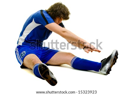 A male soccer player stretching. Studio shot over white.