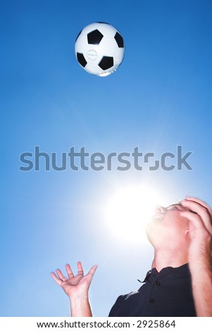 A male soccer referee or coach catching a soccer ball. The sun is shining from behind his face. There is movement on his hands and the ball but elements of the face is sharp.