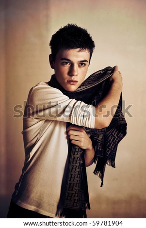 A male teen wraps a large scarf around his neck while looking pensively into the distance. Vertical shot. - stock photo